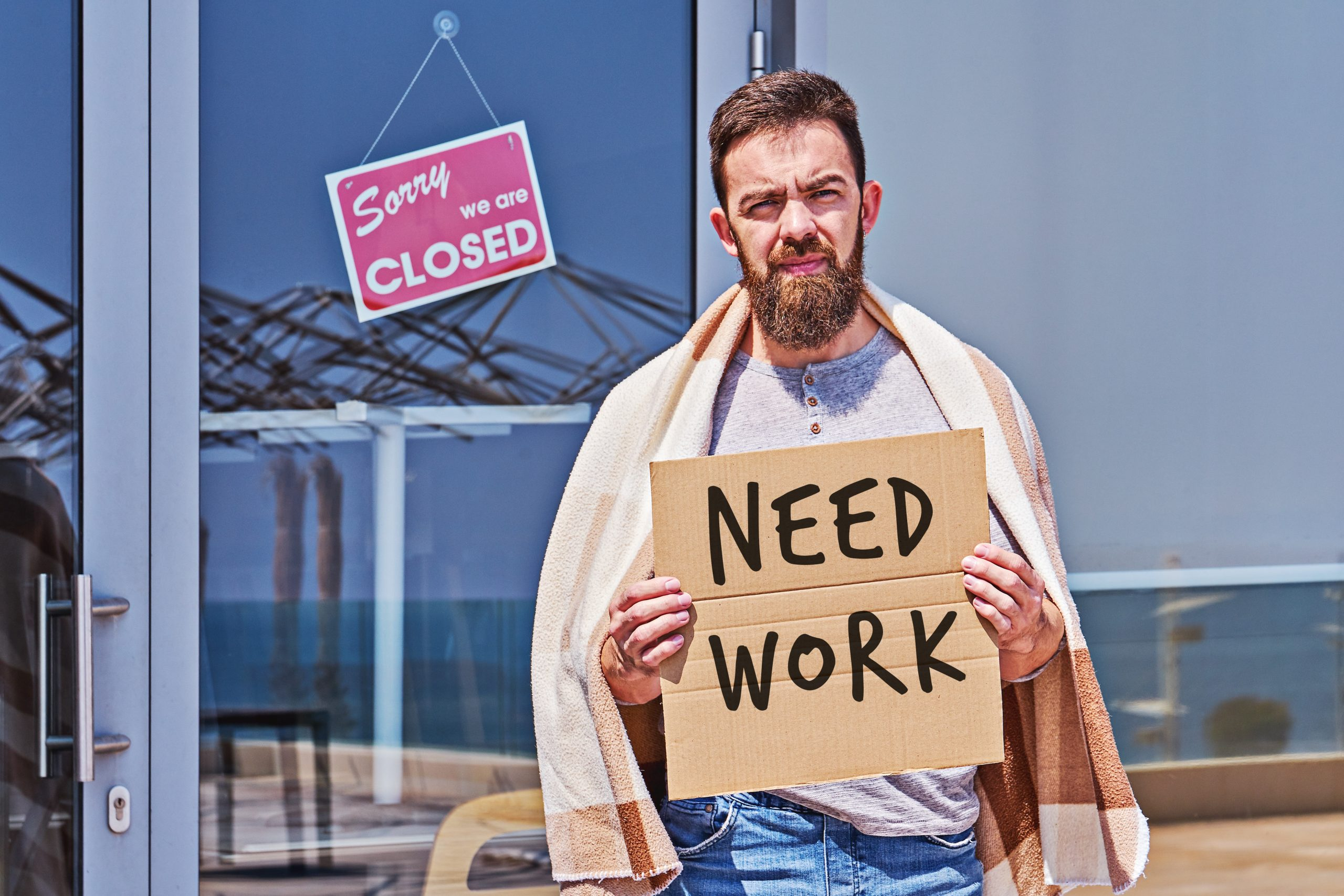 Unemployed guy with signboad NEED WORK near closed door office or cafe. Unemployment during coronavirus Covid-19 crisis, concept of job loss